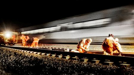 Train passing technicians working on track at night