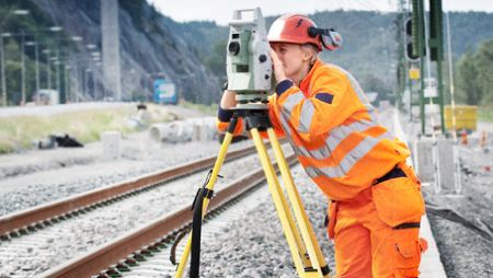 Technician uses measure device next to newly laid railroad tracks