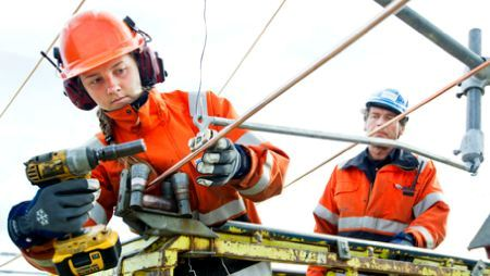 Two electricians work on a wire in a lift